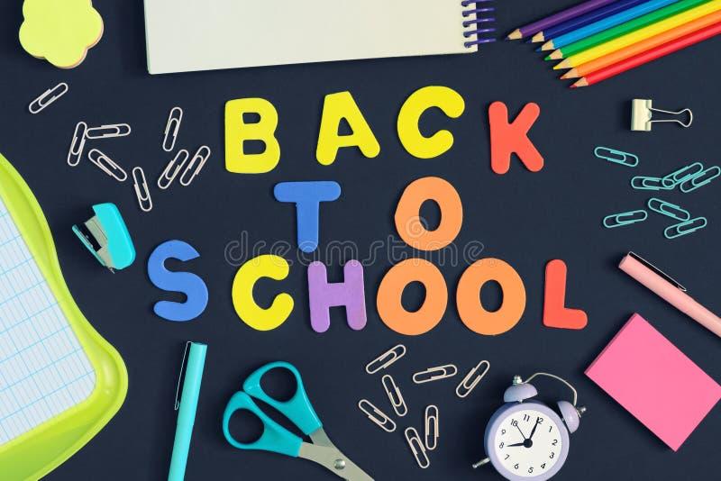 Inskriften tillbaka till skolan göras i kulöra bokstäver Mångfärgad bild på svart bakgrund fotografering för bildbyråer