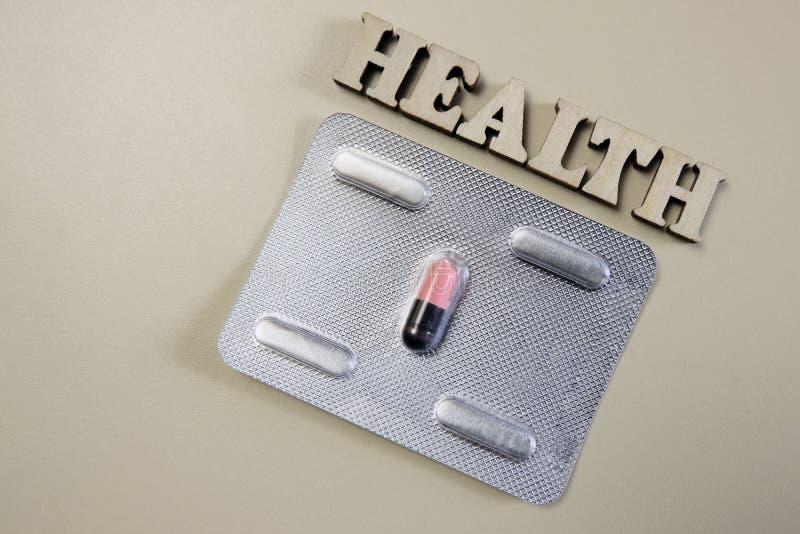 Inskrifthälsan av träbokstäver Det enda rosa och svarta pillret i en bl?sa Behandling av sjukdomen eller beroende på royaltyfria bilder