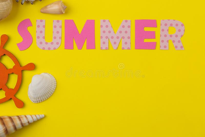Inskriftsommar från papper av mång--färgade bokstäver och snäckskal på en ljus gul bakgrund Sommar avkoppling semester fotografering för bildbyråer