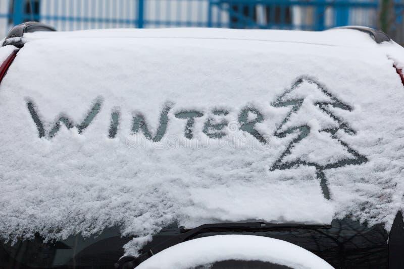 Inskriftvinter och träd på snö på det tillbaka fönstret av bilen, SUV royaltyfria foton