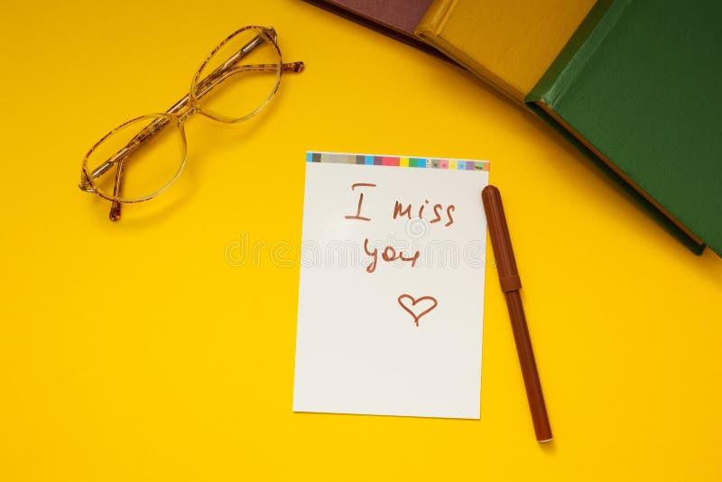 Inskrypcja «brakuję ciebie «na żółtym tle, szkłach i książkach, wpólnie fotografia royalty free