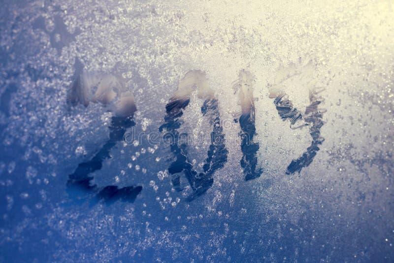 Inskrypcja 2019 na zamarzniętym okno w hoarfrost Drapał liczby na błękitnym zimnym zimy tle zdjęcie stock