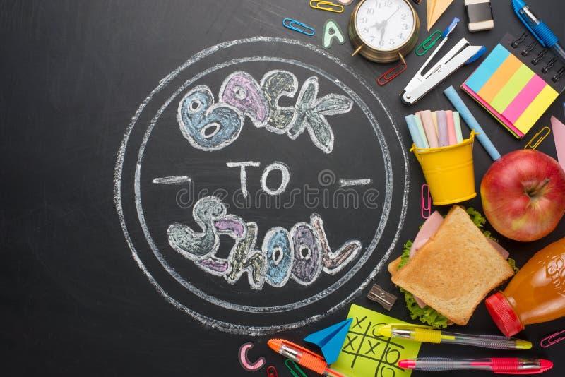 Inskrypcja z powrotem szkoła, na zarządzie szkołym z rękojeściami, kredą, budzikiem i szkoły śniadaniem, obraz stock