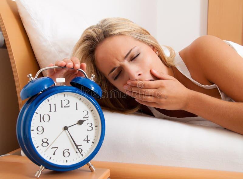 Insomne con el reloj en la noche. La mujer puede imagen de archivo libre de regalías