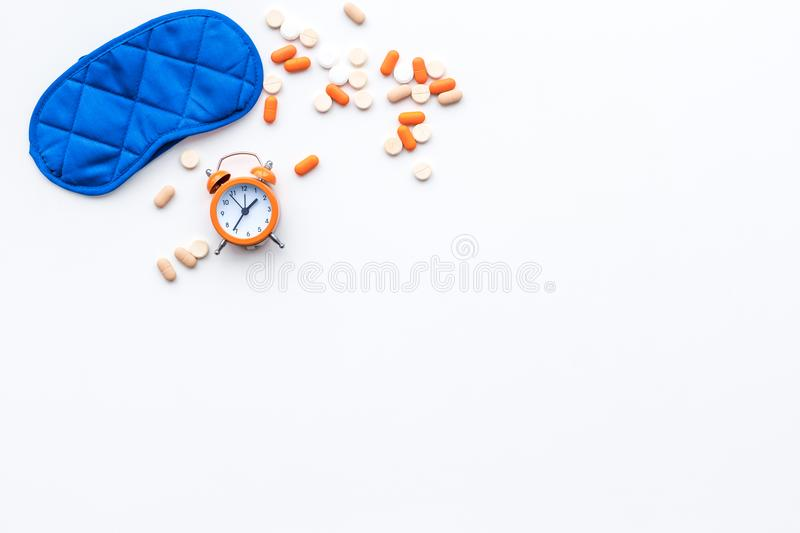 Insomnia concept. Trying to sleep. Help yourself get to sleep. Sleeping pills near sleeping mask and alarm clock on stock photography