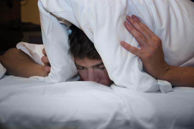 Insomniac, der seinen Kopf mit einem Kissen umfasst stockbilder