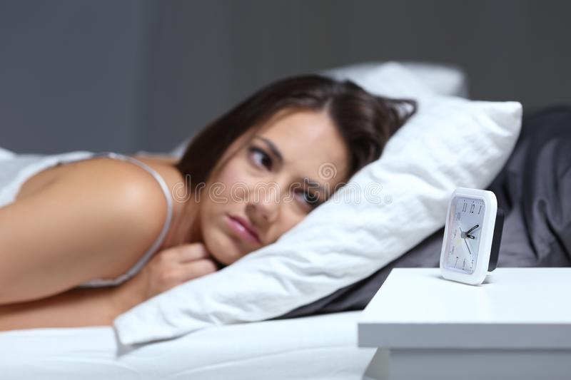 Insomniac woman looking at alarm clock in the night royalty free stock photos
