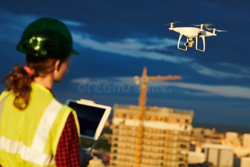Inspeção do zangão Operador que inspeciona o voo do terreno de construção da construção com zangão imagem de stock royalty free