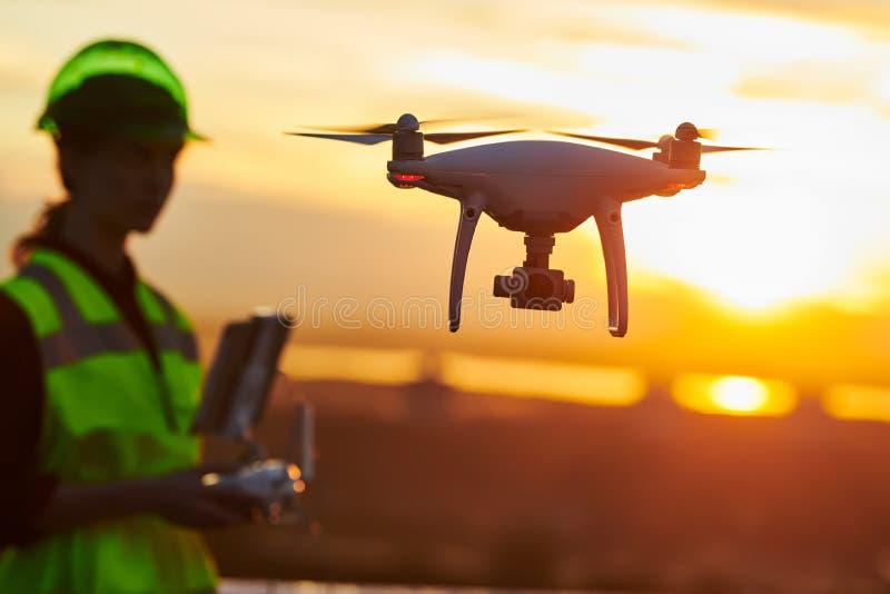 Inspeção do zangão Operador que inspeciona o voo do terreno de construção da construção com zangão Por do sol imagens de stock