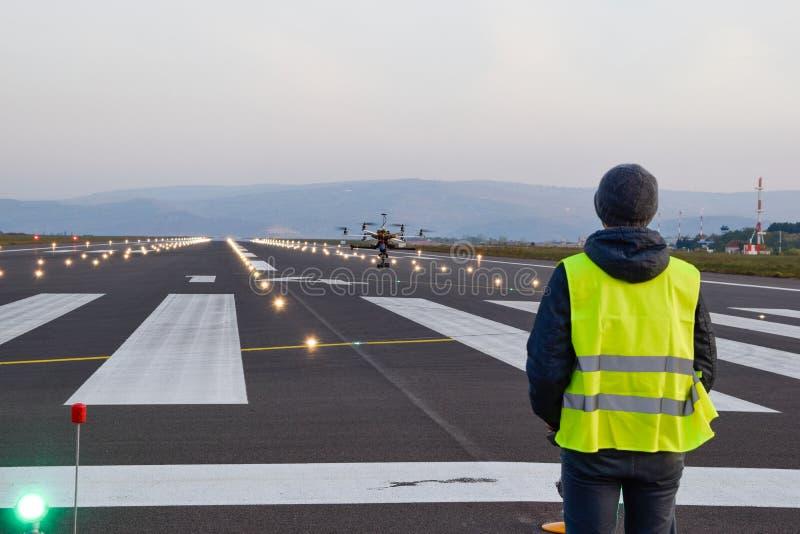 Inspeção do zangão sobre a pista de decolagem do aeroporto com operador fotografia de stock