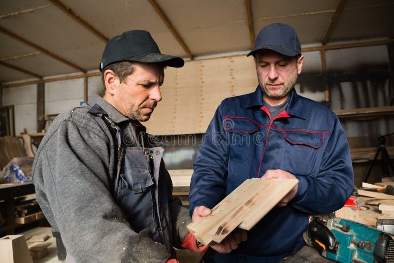 Inspecteur en timmerman in de timmerwerkworkshop stock foto