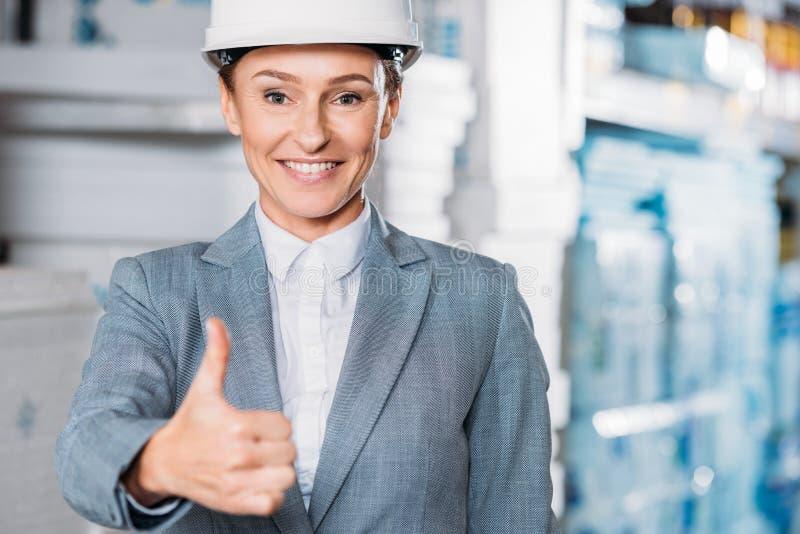 inspecteur féminin dans le pouce d'apparence de casque  images stock