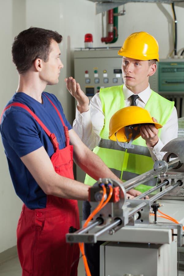 Inspecteurs controlerende veiligheid tijdens het werk bij fabriek royalty-vrije stock afbeeldingen