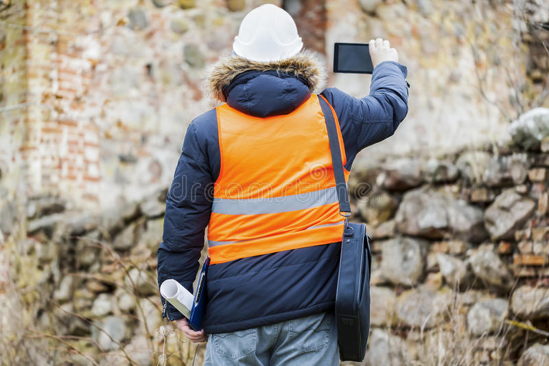 Inspecteurs des bâtiments avec la tablette à de vieilles ruines photographie stock
