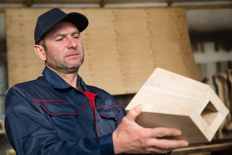 Inspecteurstimmerman die houten meubilairdeel inspecteren stock foto's
