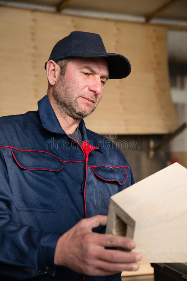 Inspecteurstimmerman die houten meubilairdeel inspecteren stock afbeeldingen
