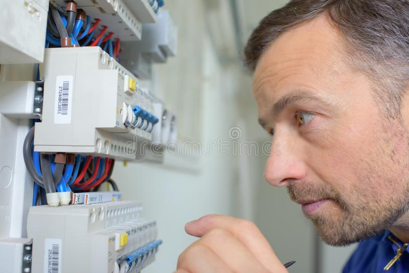 Inspecting a faulty fusebox. Arm royalty free stock photography