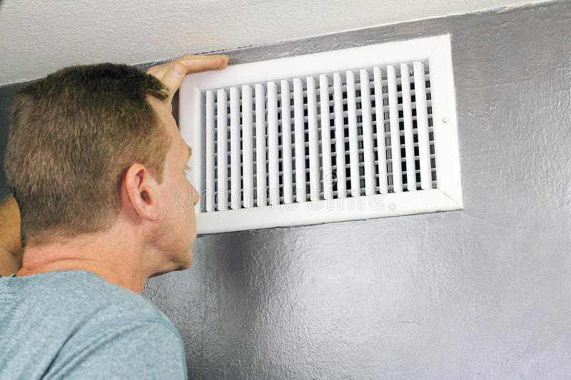 Inspecting a Home Air Vent for Maintenance. Mature man examining an outflow air vent grid and duct to see if it needs cleaning. One guy looking into a home air stock image