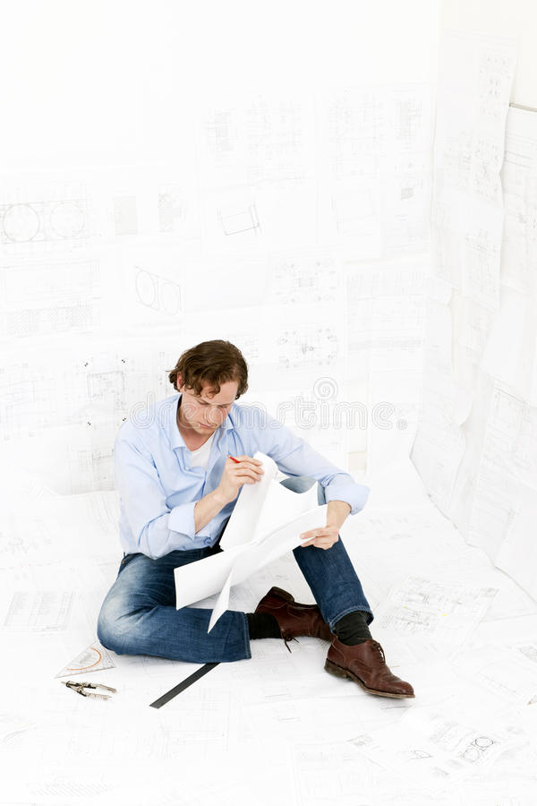Inspecting technical. Young mechanical engineer, surrounded by huge technical drawings, sitting on the floor on more designs, going over the technical details royalty free stock image