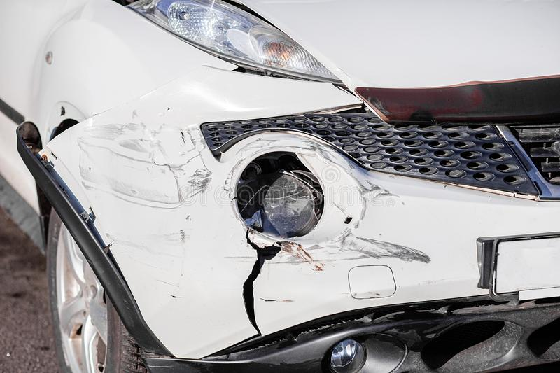 Inspection of the car after an accident on the road. The front fender and left headlight are broken, damaged and scratched on the royalty free stock photography