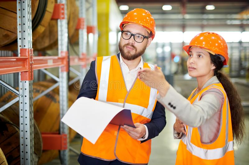 Inspection Tour at Factory. Waist up portrait of female factory worker talking to bearded businessman wearing hardhat and pointing away, copy space stock photography