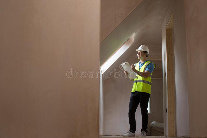 Inspector On Building Site With Clipboard. Looking Inside House royalty free stock image