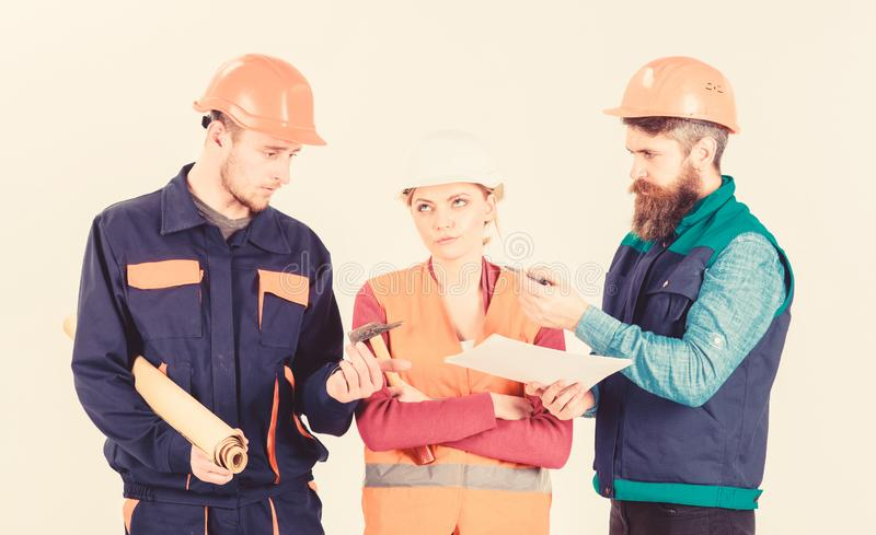 Inspector chastises employee, builder. Men and woman. Inspector chastises employee, builder. Men and women in helmets on bored face with tools and documents stock image