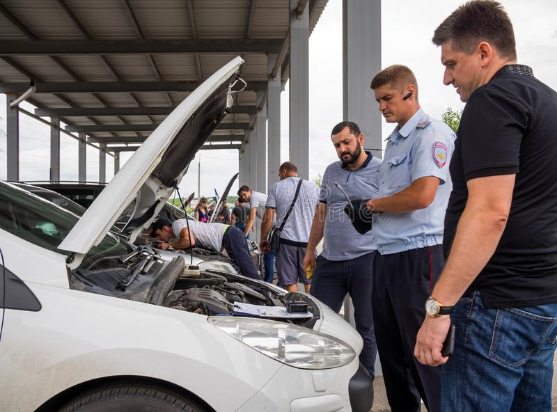 The inspector checks the vehicles on the site inspection of traffic police. Voronezh, Russia - July 17, 2018: The inspector checks the vehicles on the site royalty free stock images
