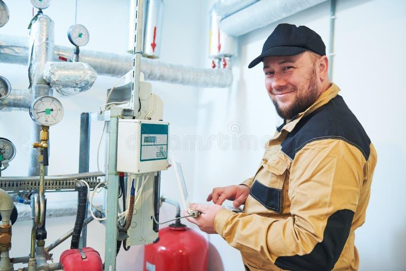 Inspector de calefacción del ingeniero o del fontanero en el sitio de caldera que toma lecturas o el ajuste del metro fotos de archivo libres de regalías