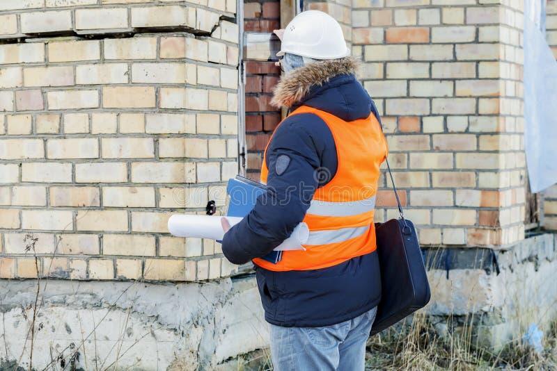 Inspector de construcción filmado en las grietas en la pared del edificio fotografía de archivo libre de regalías