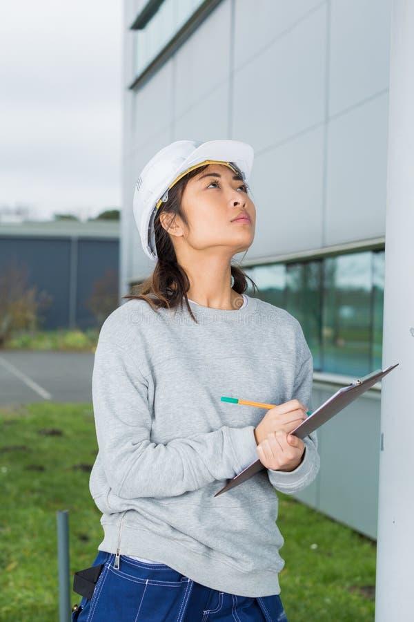 Inspector de construcción de sexo femenino asiático con el tablero fuera del edificio fotos de archivo