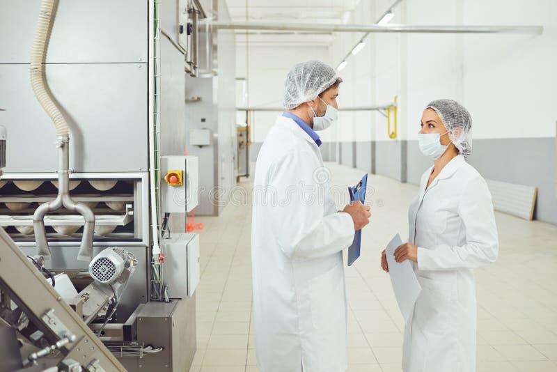 Inspector de los tecnólogos en máscaras en la fábrica de la comida imagen de archivo
