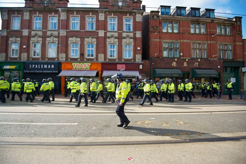 Inspector de polícia com os polícias do motim que andam ao longo da rua ocidental após um protesto foto de stock