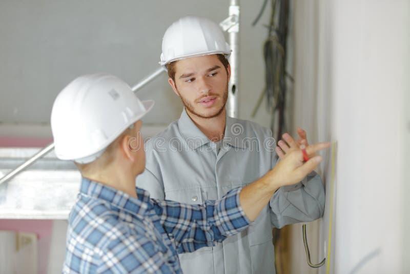 Inspector del sitio que habla con los trabajadores de construcción imagenes de archivo