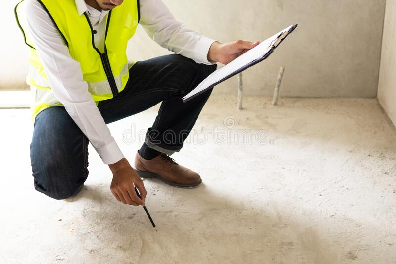 Inspector holding clipboard opening paper and checking building for renovation, engineer surveyor looking in construction site. stock image