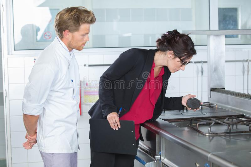 Inspector looking at gas cooker stock images