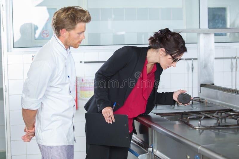 Inspector que mira la cocina de gas imagenes de archivo