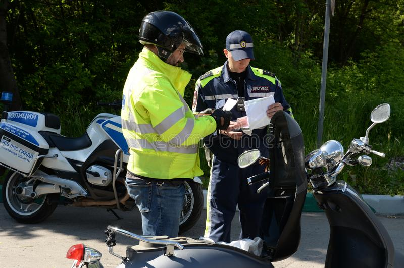 The inspector of road patrol service of police checks documents at the driver of the motor scooter stock photography