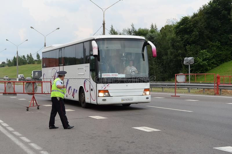 The inspector of the road police patrol stops the intercity bus for checking. MOSCOW REGION, RUSSIA - AUGUST 3,2017: The inspector of the road police patrol royalty free stock photography