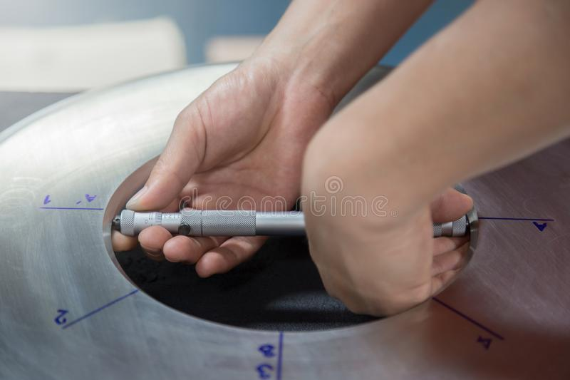 Inspector specialist using micrometer measure inside orifice stainless steel plate to check bore diameter for annual inspection.  royalty free stock photo