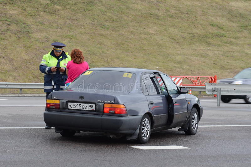 The inspector of traffic police talking with a female driver on the highway. royalty free stock images