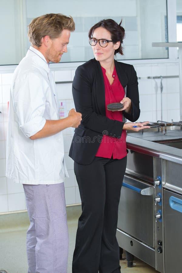 Inspector y cocinero por el horno de gas foto de archivo libre de regalías