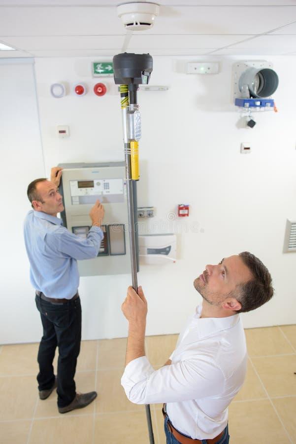 Inspectores del producto que prueban el detector de humo imagen de archivo libre de regalías