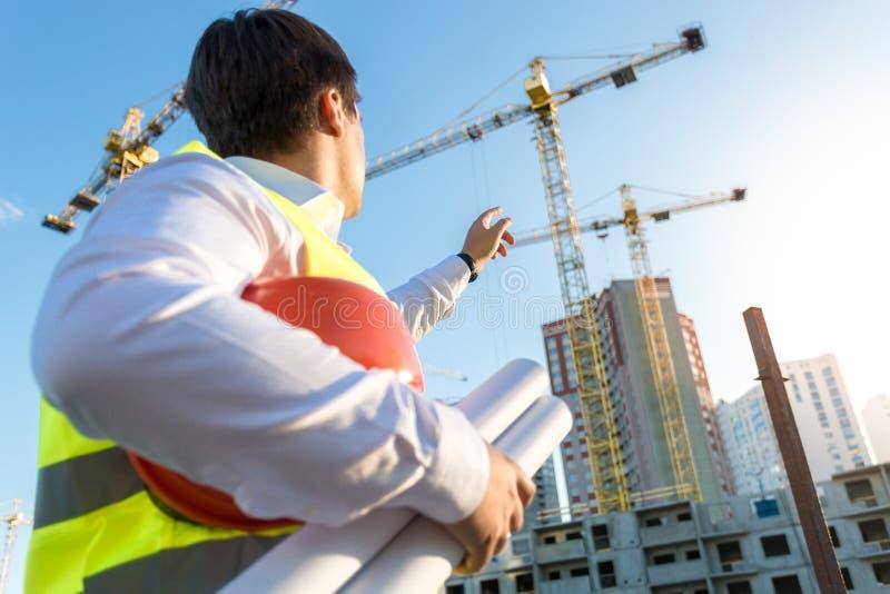 Inspektör som ser och pekar på byggnaden under constructio royaltyfri foto