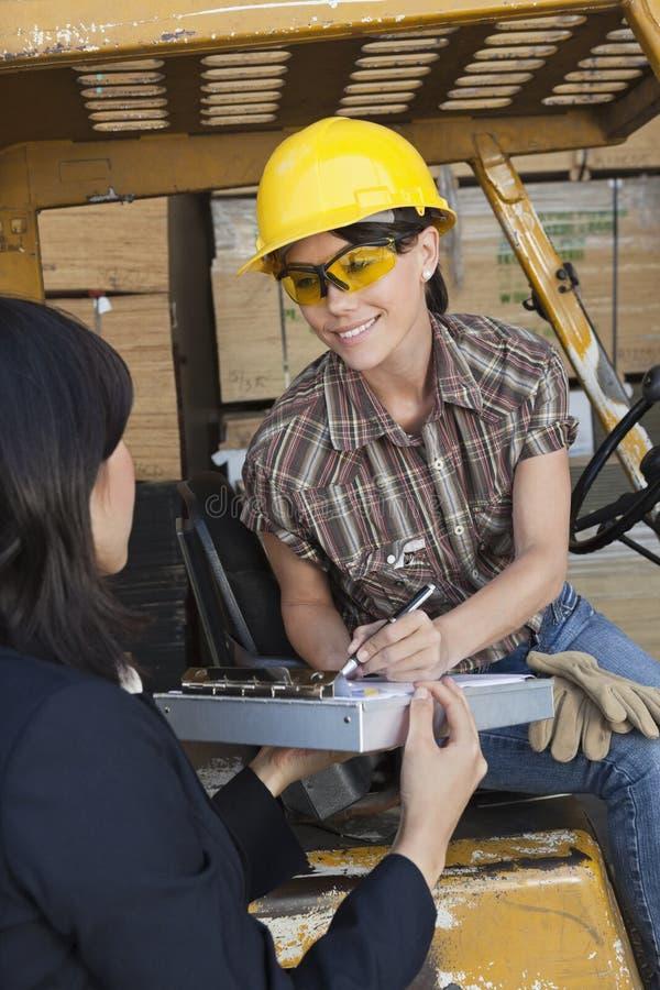 Inspektör som tar tecknet på dokument från kvinnlig lagerarbetare arkivbild