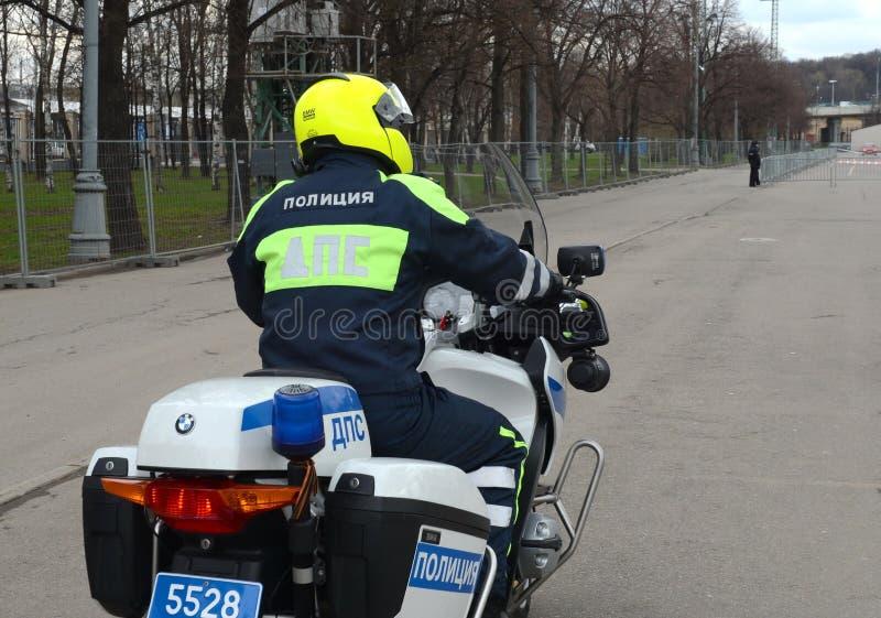 Inspektören av vägpolispatrullen på den tjänste- motorcykeln kontrollerar vägen royaltyfria bilder
