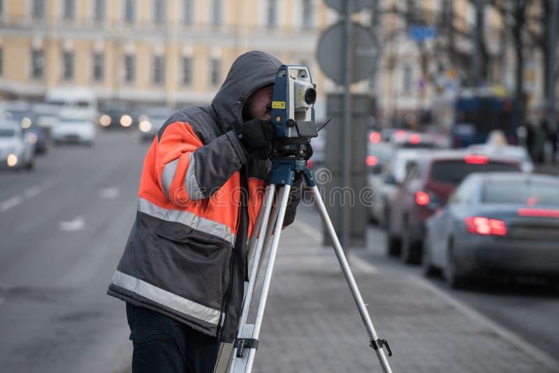 Inspektören med teodoliten gör mätningar i centen arkivbilder