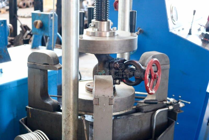 Inspektion von Rohrleitungsventilen, Ventile auf einem großen automatischen Metall drücken die Produktionsanlage ein Konzeptindus stockfotografie