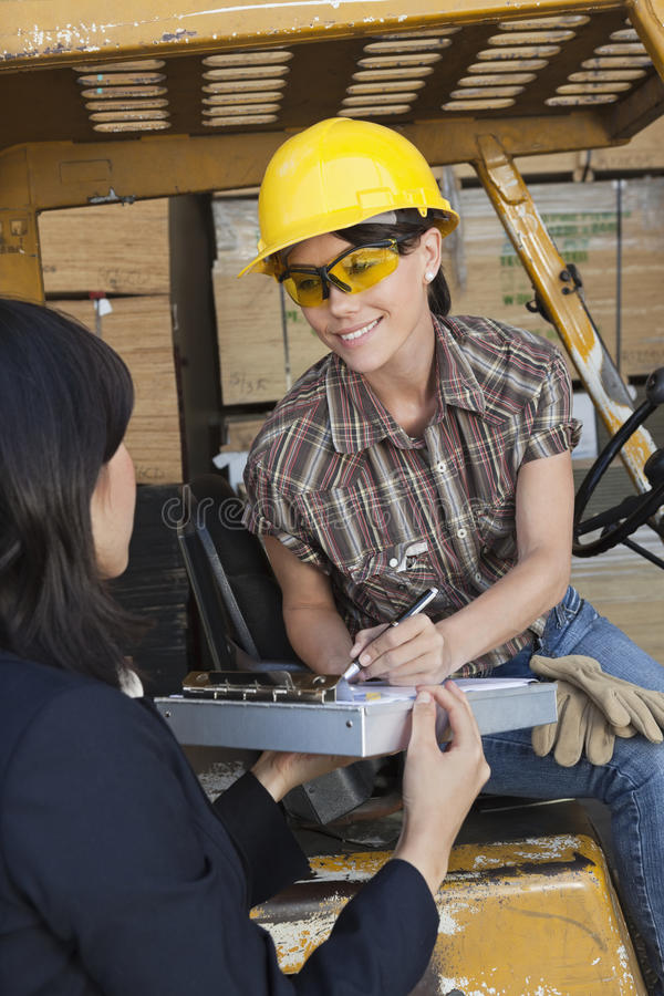 Inspektorski bierze znak na dokumencie od kobieta magazynu pracownika fotografia stock