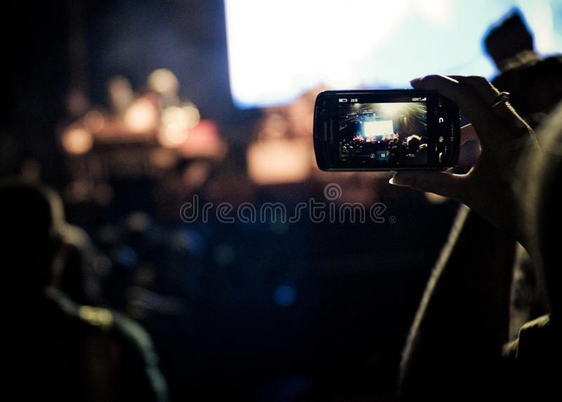 Inspelningmusikhändelsen bor på en smartphonetelefon på en festival för öppen luft royaltyfria foton